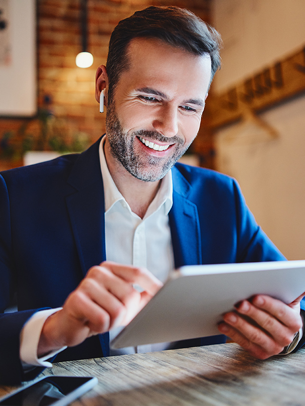 Businessman sitting in cafe looking at tablet during phone call through wireless headphones for Offload Business Solutions Human Resources and Payroll Services in Jacksonville, FL